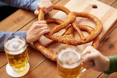Κλείστε επάνω των ατόμων που πίνουν την μπύρα με pretzels στο μπαρ Στοκ Εικόνα