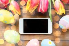 Κλείστε επάνω των αυγών Πάσχας, των λουλουδιών και του smartphone Στοκ Εικόνες