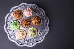 Κλείστε επάνω των γλυκών ζωηρόχρωμων cupcakes στο πιάτο γυαλιού πέρα από γκρίζο στοκ εικόνες