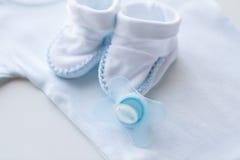 Κλείστε επάνω των ενδυμάτων soother και μωρών για νεογέννητο Στοκ Φωτογραφία