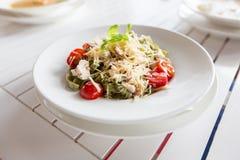 Κλείστε επάνω των ζυμαρικών με την ντομάτα και του τυριού στο πιάτο Στοκ Φωτογραφίες