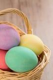 Κλείστε επάνω των ζωηρόχρωμων αυγών Πάσχας σε ένα ψάθινο καλάθι Στοκ Εικόνες