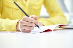 Κλείστε επάνω των θηλυκών χεριών γράφοντας στο σημειωματάριο Στοκ εικόνα με δικαίωμα ελεύθερης χρήσης