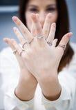 Κλείστε επάνω των θηλυκών χεριών με τα δαχτυλίδια Στοκ Φωτογραφίες