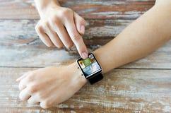 Κλείστε επάνω των θηλυκών χεριών με τις ειδήσεις στο έξυπνο ρολόι στοκ εικόνα