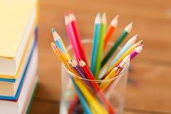 Κλείστε επάνω των κραγιονιών ή χρωματίστε τα μολύβια και τα βιβλία Στοκ Εικόνες