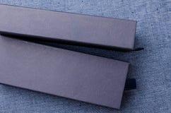 Κλείστε επάνω των μπλε κιβωτίων στο μπλε υπόβαθρο υφάσματος Στοκ Εικόνες