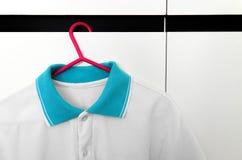 Κλείστε επάνω των μπλουζών στις κρεμάστρες υφασμάτων Στοκ Φωτογραφία
