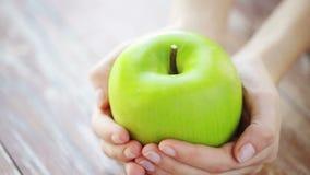 Κλείστε επάνω των νέων χεριών γυναικών που παρουσιάζουν πράσινο μήλο φιλμ μικρού μήκους