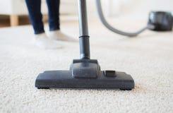 Κλείστε επάνω των ποδιών γυναικών με την ηλεκτρική σκούπα στο σπίτι Στοκ Φωτογραφία