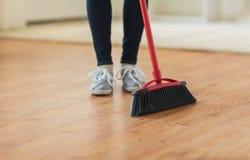Κλείστε επάνω των ποδιών γυναικών με το σκουπίζοντας πάτωμα σκουπών Στοκ εικόνα με δικαίωμα ελεύθερης χρήσης
