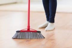 Κλείστε επάνω των ποδιών γυναικών με το σκουπίζοντας πάτωμα σκουπών Στοκ φωτογραφία με δικαίωμα ελεύθερης χρήσης
