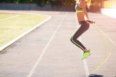 Κλείστε επάνω των ποδιών γυναικών πηδώντας, χρησιμοποιώντας το πηδώντας σχοινί στο στάδιο Στοκ Φωτογραφίες