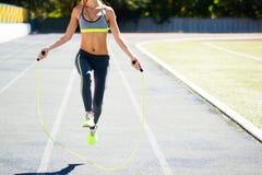 Κλείστε επάνω των ποδιών γυναικών πηδώντας, χρησιμοποιώντας το πηδώντας σχοινί στο στάδιο Στοκ Εικόνες