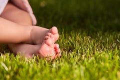 Κλείστε επάνω των ποδιών μωρών ` s στην πράσινη χλόη στο λιβάδι στη θερμή ημέρα Στοκ Εικόνα