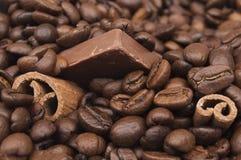 Κλείστε επάνω των συσσωρευμένων φασολιών καφέ, των ραβδιών κανέλας και της σοκολάτας στοκ εικόνες