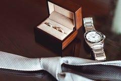 Κλείστε επάνω των σύγχρονων εξαρτημάτων νεόνυμφων γαμήλια δαχτυλίδια σε ένα καφετιά ξύλινα κιβώτιο, μια γραβάτα και ένα ρολόι Στοκ φωτογραφία με δικαίωμα ελεύθερης χρήσης