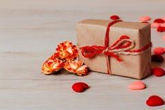 Κλείστε επάνω των φωτεινών μικρών καρδιών, των λουλουδιών άνοιξη και του τυλιγμένου δώρο σχοινιού τεχνών στο ξύλινο υπόβαθρο Στοκ Εικόνες