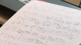 Κλείστε επάνω των χειρόγραφων σημειώσεων τζαζ μουσικής κοντά στα κλειδιά πιάνων απόθεμα βίντεο