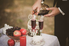 Κλείστε επάνω των χεριών ατόμων κρατώντας το μπουκάλι του κόκκινου κρασιού Στοκ Εικόνα
