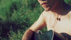 Κλείστε επάνω των χεριών ατόμων παίζοντας την κιθάρα στη φύση 4K απόθεμα βίντεο