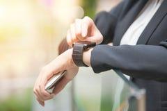 Κλείστε επάνω των χεριών γυναικών θέτοντας smartwatch έξω Στοκ εικόνες με δικαίωμα ελεύθερης χρήσης