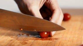 Κλείστε επάνω των χεριών γυναικών κόβοντας τις ντομάτες κερασιών, βαθμολογημένο 4k φιλμ μικρού μήκους