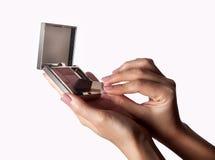 Κλείστε επάνω των χεριών γυναικών με την εκμετάλλευση βουρτσών makeup κοκκινίζει Το θηλυκό κράτημα χεριών κοκκινίζει κιβώτιο και  Στοκ φωτογραφίες με δικαίωμα ελεύθερης χρήσης