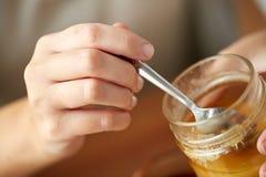 Κλείστε επάνω των χεριών γυναικών με το μέλι και το κουτάλι Στοκ φωτογραφία με δικαίωμα ελεύθερης χρήσης