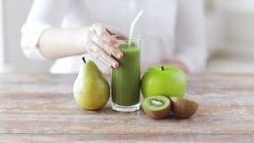 Κλείστε επάνω των χεριών γυναικών με το χυμό και τα φρούτα