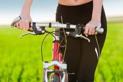 Κλείστε επάνω των χεριών γυναικών που στηρίζονται στο ποδήλατο Στοκ Εικόνες