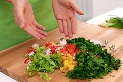 Κλείστε επάνω των χεριών γυναικών ` s που μαγειρεύουν στην κουζίνα Νοικοκυρά που προσφέρει τη φρέσκια σαλάτα Χορτοφάγος και εποικ Στοκ φωτογραφία με δικαίωμα ελεύθερης χρήσης