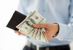 Κλείστε επάνω των χεριών επιχειρηματιών κρατώντας τα χρήματα Στοκ Εικόνες
