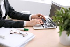 Κλείστε επάνω των χεριών επιχειρησιακών γυναικών δακτυλογραφώντας στο φορητό προσωπικό υπολογιστή στο άσπρο χρωματισμένο γραφείο στοκ φωτογραφία