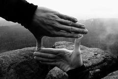 Κλείστε επάνω των χεριών κάνοντας τη χειρονομία πλαισίων Μπλε misty δύσκολη αιχμή φυσητήρων κοιλάδων Βροχερή ημέρα άνοιξη Στοκ Εικόνα