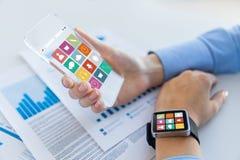 Κλείστε επάνω των χεριών με τα έξυπνα εικονίδια τηλεφώνων και ρολογιών Στοκ Εικόνες