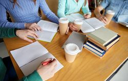 Κλείστε επάνω των χεριών με τα βιβλία γράφοντας στα σημειωματάρια Στοκ Εικόνες