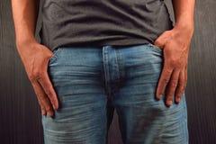 Κλείστε επάνω των χεριών με τα μεγάλα δάχτυλα στις τσέπες του μπλε je του Στοκ Εικόνες