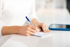 Κλείστε επάνω των χεριών με τη μάνδρα γράφοντας στο σημειωματάριο Στοκ Εικόνες