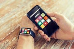 Κλείστε επάνω των χεριών με το έξυπνα τηλέφωνο και το ρολόι Στοκ Φωτογραφίες