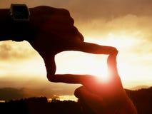 Κλείστε επάνω των χεριών με το ρολόι κάνοντας τη χειρονομία πλαισίων Σκοτεινός misty φυσητήρας κοιλάδων στο τοπίο Στοκ Φωτογραφίες