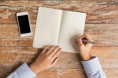 Κλείστε επάνω των χεριών με το σημειωματάριο και το smartphone Στοκ εικόνα με δικαίωμα ελεύθερης χρήσης