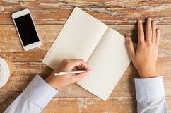 Κλείστε επάνω των χεριών με το σημειωματάριο και το smartphone Στοκ Εικόνες