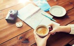 Κλείστε επάνω των χεριών με το φλυτζάνι καφέ και την ουσία ταξιδιού Στοκ Φωτογραφίες