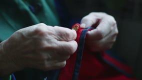 Κλείστε επάνω των χεριών μιας πολύ ηλικιωμένης γυναίκας ράβει πλήκτρο τα ΟΝ απόθεμα βίντεο