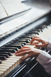 Κλείστε επάνω των χεριών νέων κοριτσιών, παίζοντας το πιάνο Στοκ Φωτογραφία
