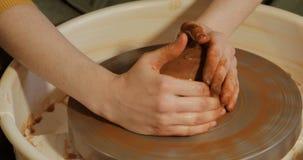 Κλείστε επάνω των χεριών που λειτουργούν τον άργιλο στη ρόδα αγγειοπλαστών ` s απόθεμα βίντεο