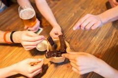 Κλείστε επάνω των χεριών που παίρνουν το πρόχειρο φαγητό ψωμιού σκόρδου Στοκ Εικόνες
