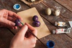 Κλείστε επάνω των χεριών που χρωματίζουν τα αυγά Στοκ εικόνα με δικαίωμα ελεύθερης χρήσης