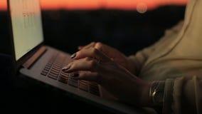 Κλείστε επάνω των χεριών της γυναίκας δακτυλογραφώντας στο πληκτρολόγιο του lap-top στο ηλιοβασίλεμα Νέα επιχειρησιακή γυναίκα στ απόθεμα βίντεο